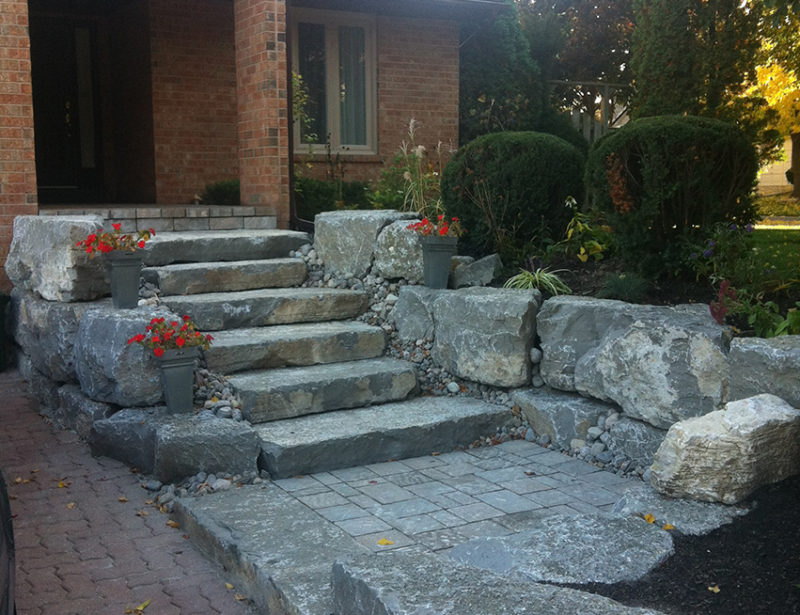 A shot of a front entrance to a home owner's house. We allowed them to entering the house from the centre of their driveway, using natural armour stone and giant flagstone steps. Finished off with a wet lay of interlocking over their front porch.