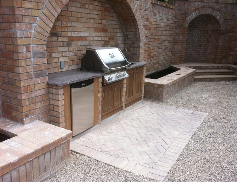 An outdoor kitchen, with an interlocking pad, and a pea gravel pathway.