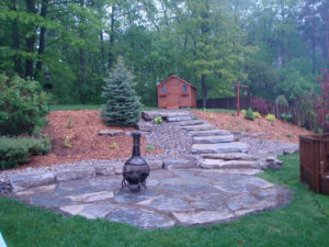 A total remake of a backyard. The grade was redone, install large Blue spruce, with large mulch beds. Also a shed on the top of the hill, and oversized natural stone giant flag steps up. Allowing the home owner to turn their backyard into a beautiful natural oasis.