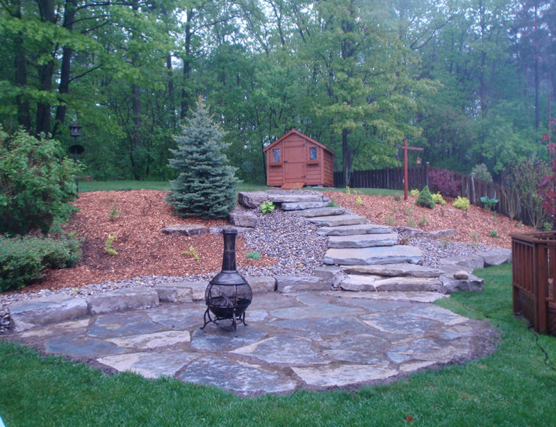 A total remake of a backyard. The grade was redone, install large Blue spruce, with large mulch beds. Also a shed on the top of the hill, and oversized natural stone giant flag steps up. Allowing the home owner to turn their backyard into a beautiful natural oasis. Located in Holland Landing.