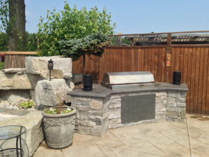 This is a shot of an outdoor BBQ set in natural granite stone and with an armour stone backing.